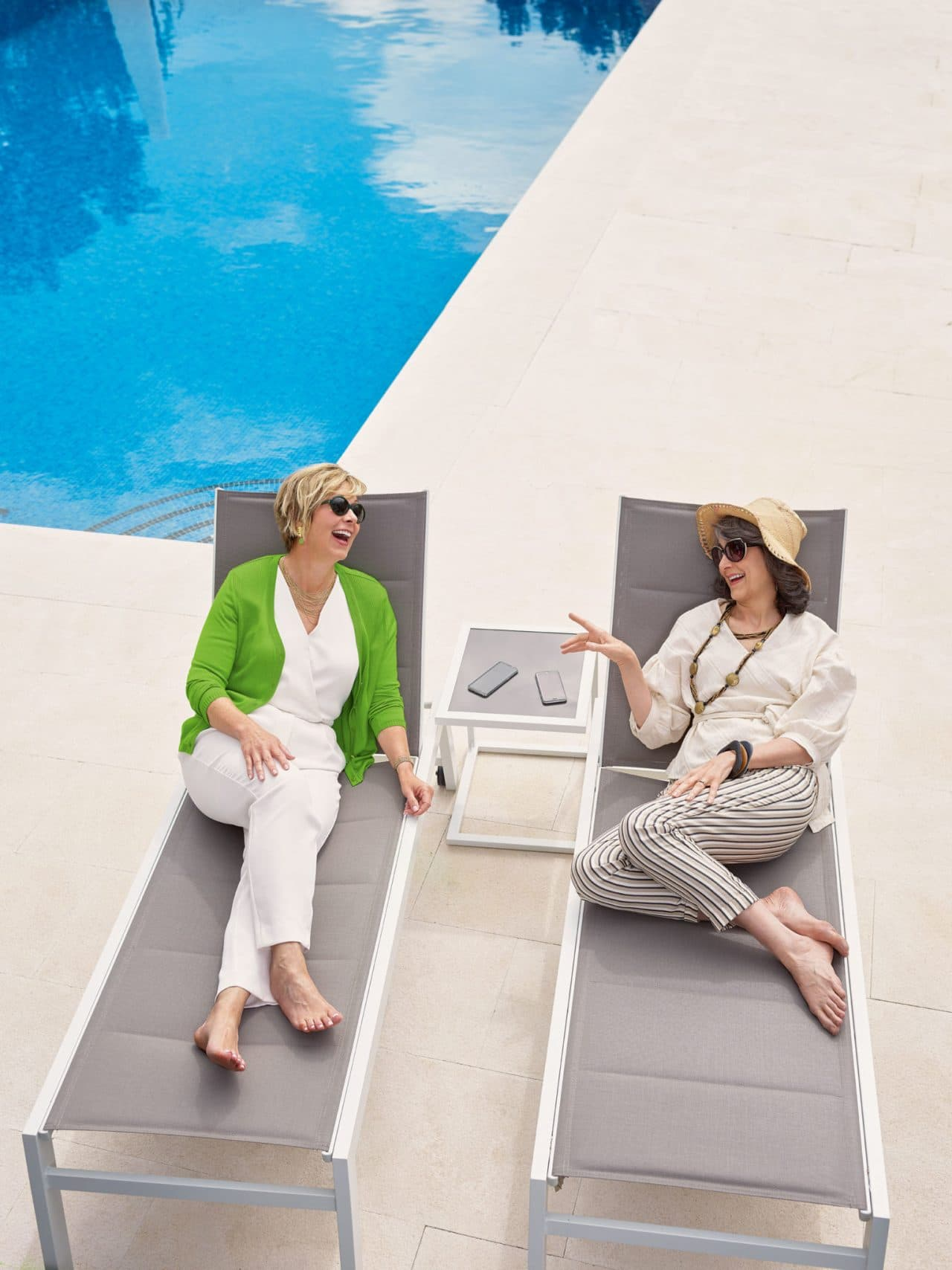 Photo of two women talking and smiling next to a pool