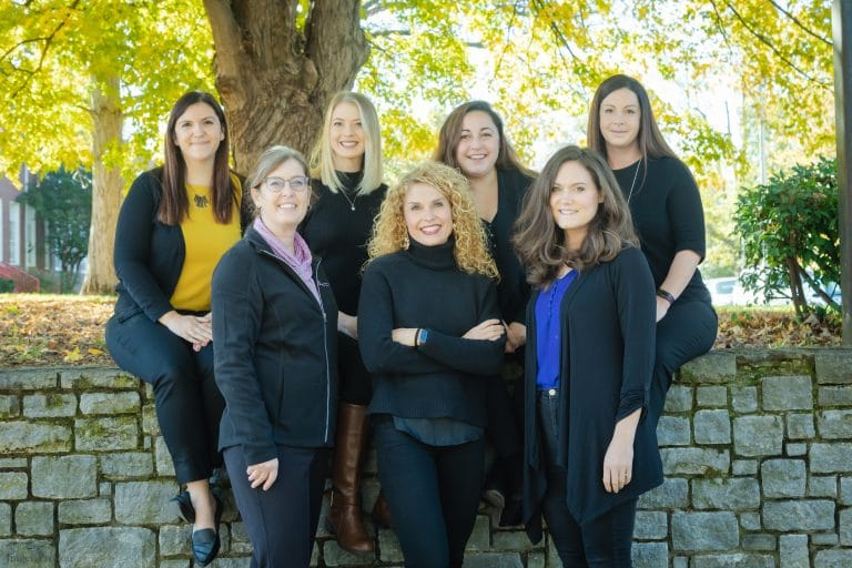 Photo of the staff at The Hearing & Speech Center: seven women smiling in two lines outside