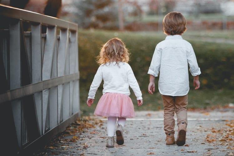Two children walking on a bridge
