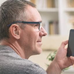 Man with a hearing aid uses his phone.